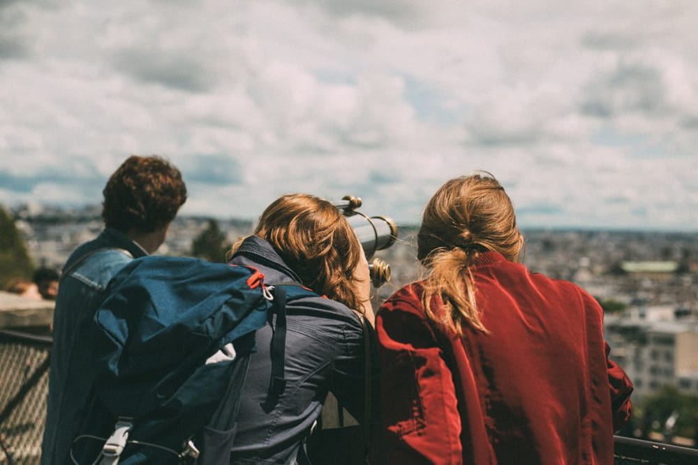 Three young people observing the views from the top of a hill